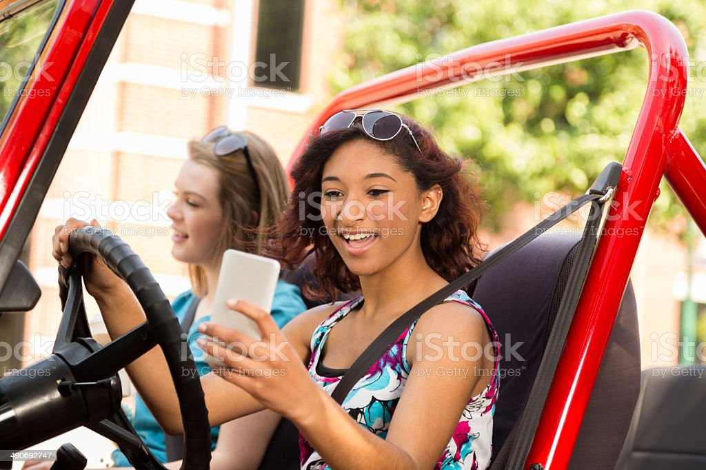 Distracted, mixed-race teenage girl texting while driving a car. stock photo