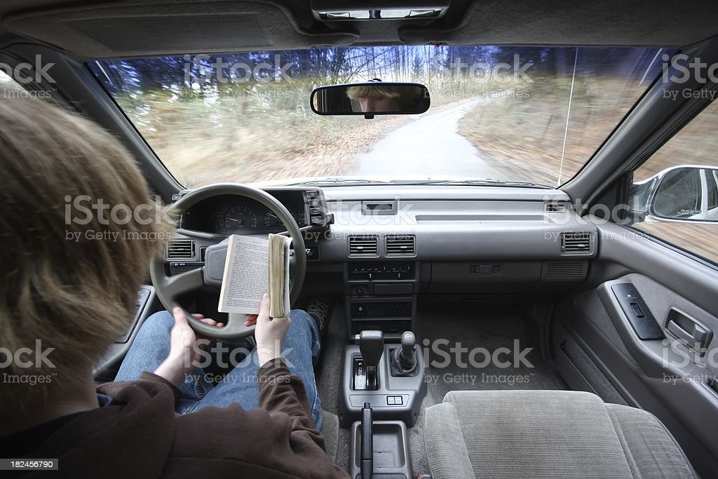 Distracted Teen Driver - Reading royalty-free stock photo