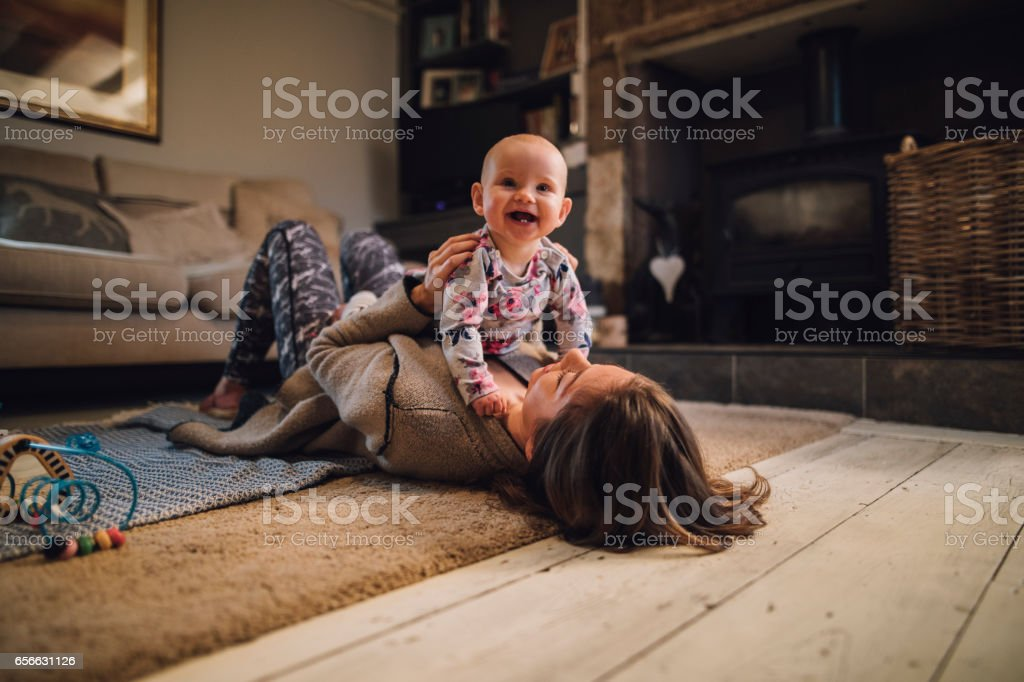 Distracting Mum From Yoga Baby girl is laughing and looking at the camera as her mother holds her on her chest. The mother is lying on the floor wearing yoga clothing. 30-39 Years Stock Photo