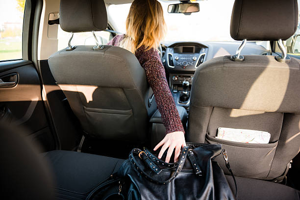 Distraction - reaching purse while driving stock photo