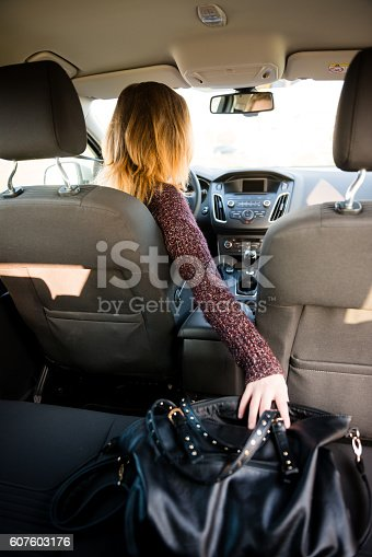 607592606 istock photo Distraction - reaching purse while driving 607603176