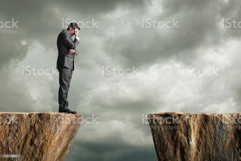 Distraught businessman standing at the edge of a cliff stock photo