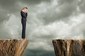 A distraught businesswoman standing at the edge of a cliff with her head in his hands. She is struggling with the fact that she can't get to the other side. Room for text.