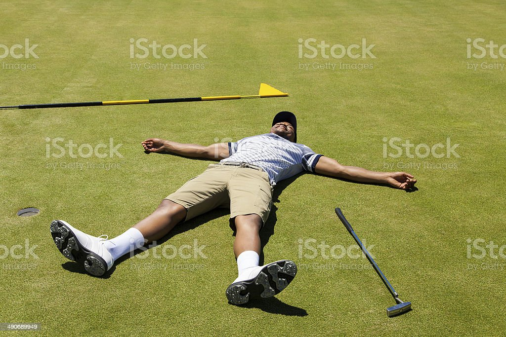 Distraught golfer lying on putting green. stock photo