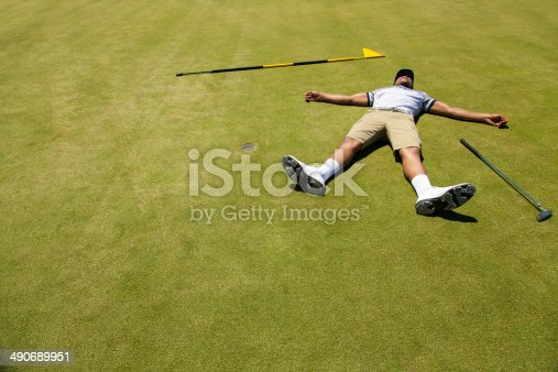 African golfer lying on putting green with his arms and legs open wide feeling exhausted. Langebaan, Western Cape, South Africa