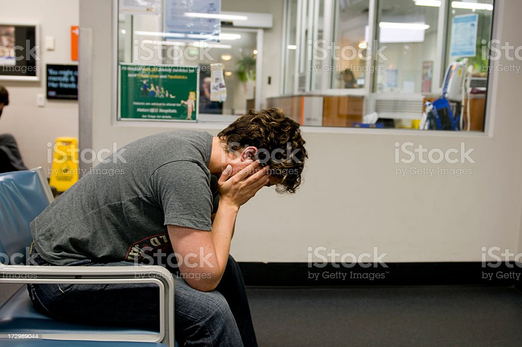 Distraught man sitting in a waiting room covering his face stock photo