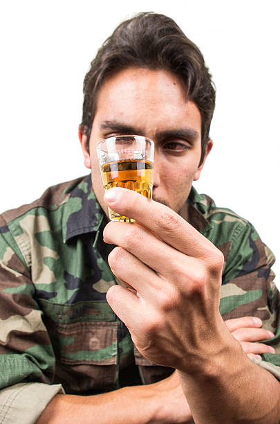 distraught military soldier veteran ptsd drinking a shot of liquor distraught military soldier veteran ptsd drinking a shot of liquor solated on white mount combatant stock pictures, royalty-free photos & images