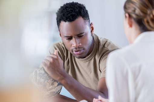 istock Distraught military veteran talks with counselor 872120584