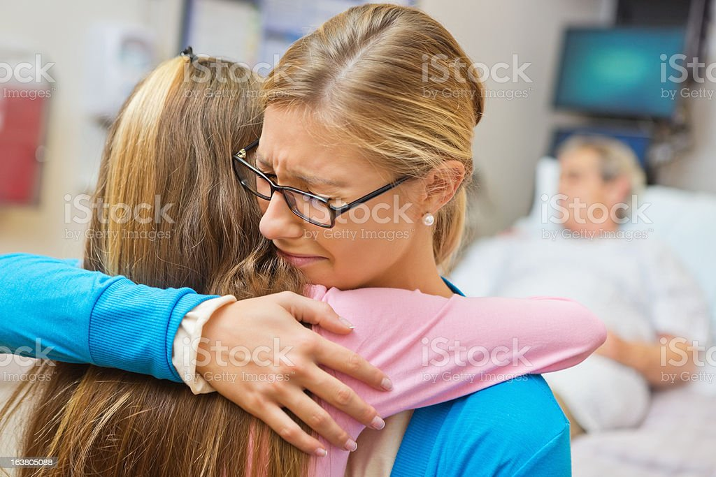 Distraught mom comforting daughter in sick senior man's hospital room royalty-free stock photo