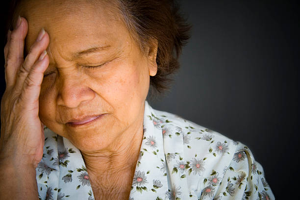 Distraught, pained older woman, eyes closed, hand to brow stock photo