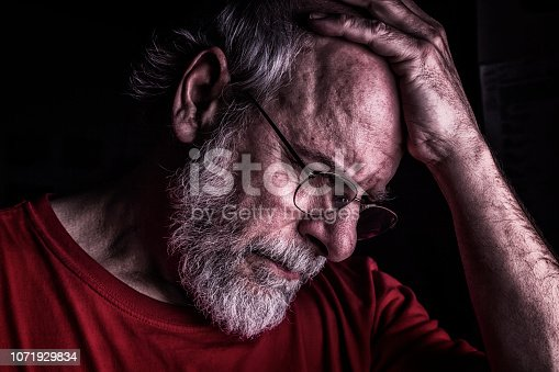 A distraught senior adult man is holding his head with his hand as he looks down.