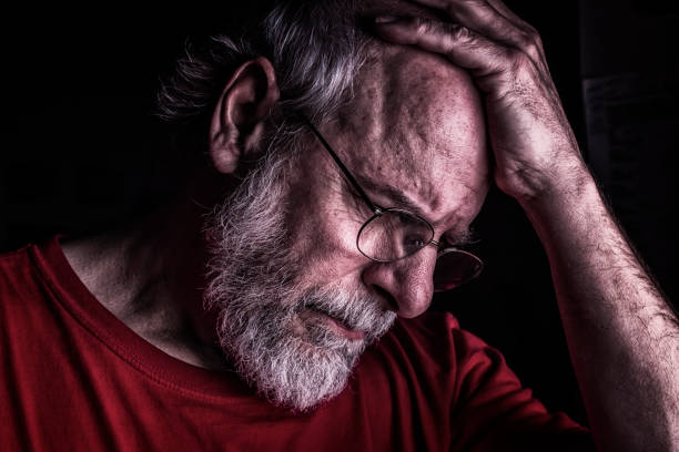 Distraught Senior Adult Man Holding Head stock photo