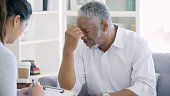 istock Distraught senior man meets with mental health professional 1031623336