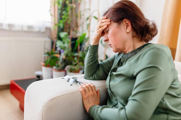 ein verstörter senior woman leidet unter einer migräne - schwindelig stock-fotos und bilder