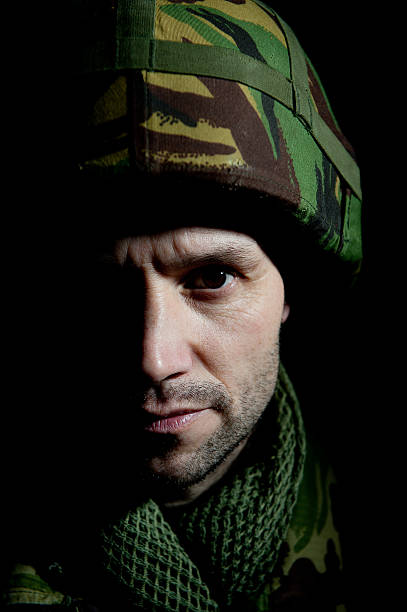 Distraught Soldier Portrait Portrait of a slightly distraught British soldier with half his face in shadow, against a black background. mount combatant stock pictures, royalty-free photos & images