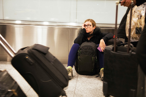 Distraught woman sits in airport while travelers pass her