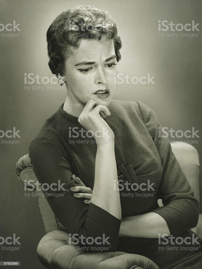 Distraught woman sitting in armchair in studio, (B&W), portrait royalty-free stock photo