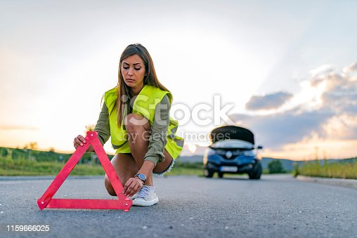 istock Distraught young girl with broken-down car 1159666025