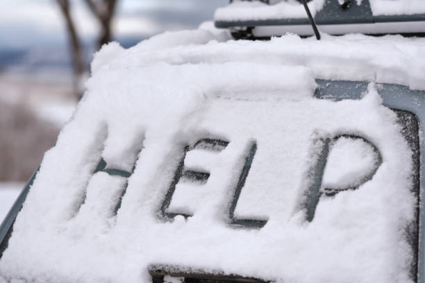 """HELP distress message written on car in snow The word """"HELP"""" is written on a car stranded in the snow aground stock pictures, royalty-free photos & images"""