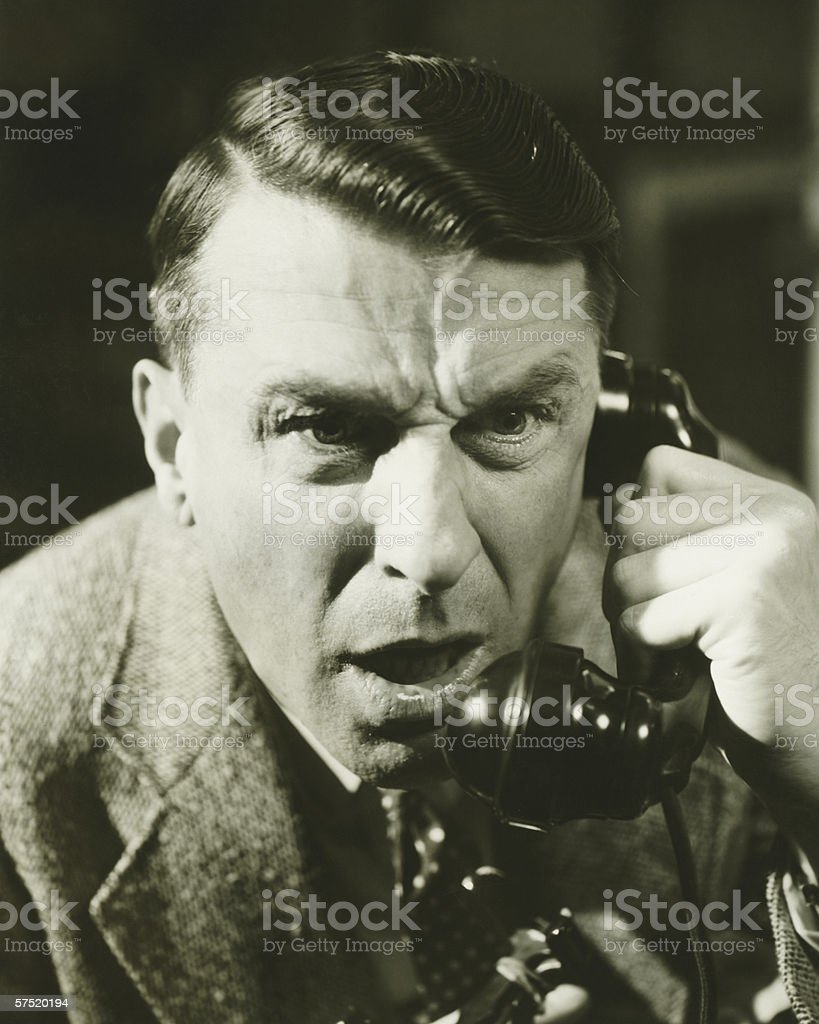 Distressed man on landline phone, (B&W), close-up royalty-free stock photo