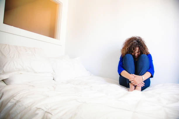 Distressed Mature Caucasian female sitting on her bed in fetal position Distressed Mature Caucasian female sitting on her bed in fetal position drug rehab stock pictures, royalty-free photos & images