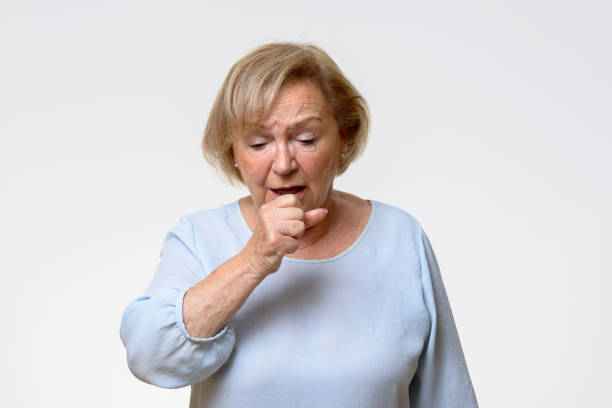 Distressed senior woman coughing stock photo