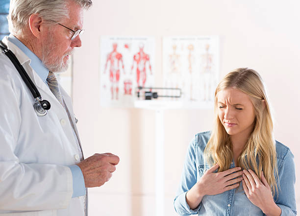 A distressed women describing her symptoms to a doctor stock photo