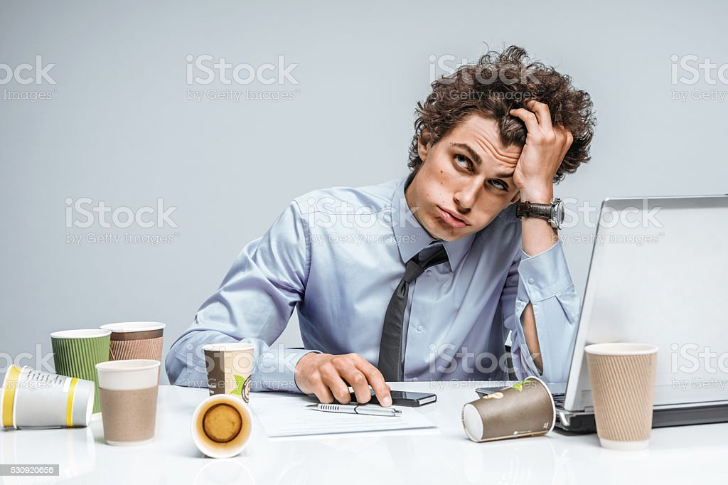 Distressed young manager man holds her head with hand stock photo