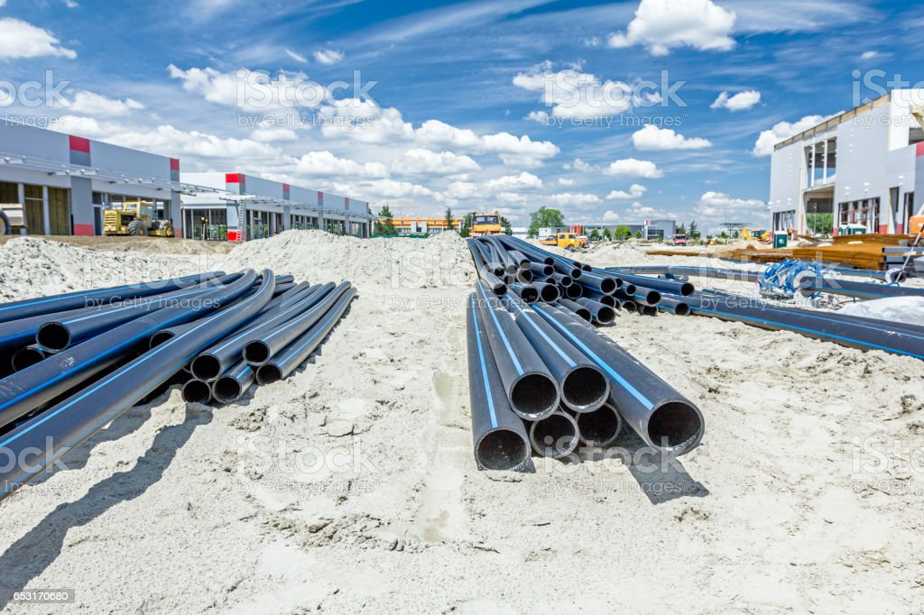 Distributed plastic pipes are stacked, piled temporarily at building site stock photo