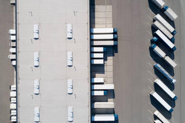 Distributionslager und LKWs von oben – Foto