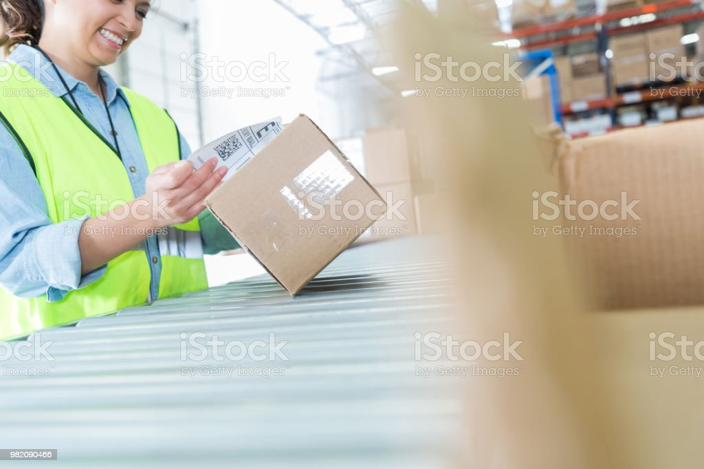 Mid adult female distribution worker attaches mailing label to a...