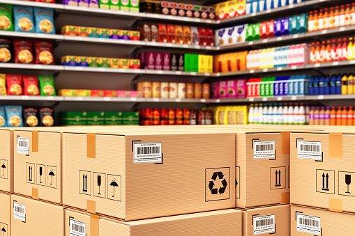 Stack of cardboard boxes in a retail store on the background of shelves with goods