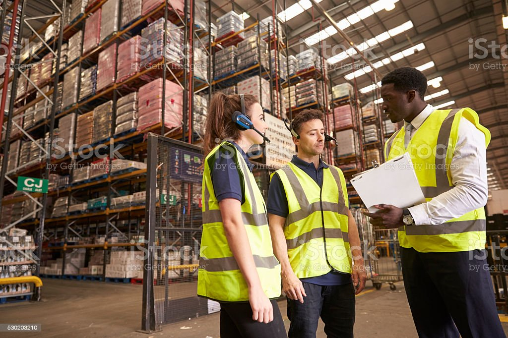 Distribution warehouse manager in discussion with colleagues stock photo