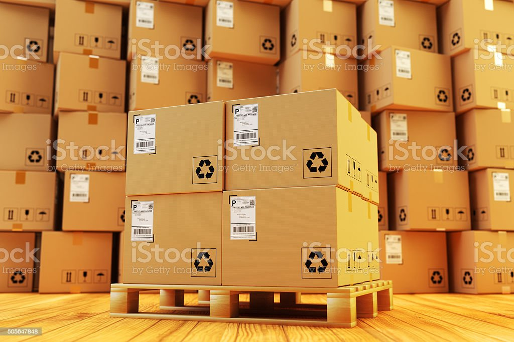 Cardboard boxes on pallet and stack of parcels behind it on wooden...