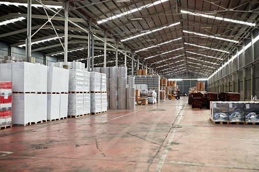 Wide angle view of merchandise stored in large organized warehouse management system.