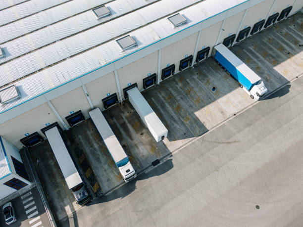 Distribution warehouse with loading docks and trucks as seen from above stock photo