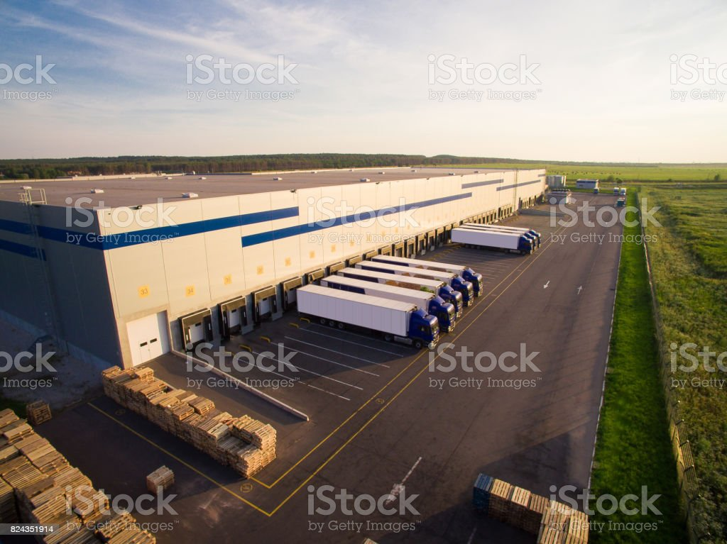 distribution warehouse with trucks of different capacity stock photo