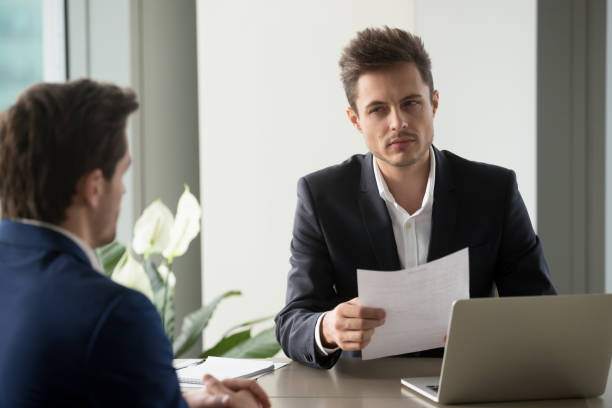 Distrustful businessman holding document, reading bad resume at job interview stock photo
