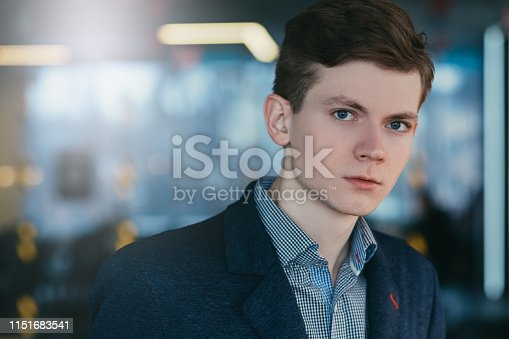 Closeup portrait of distrustful young man beginning his career. Sceptic facial expression. Copy space.