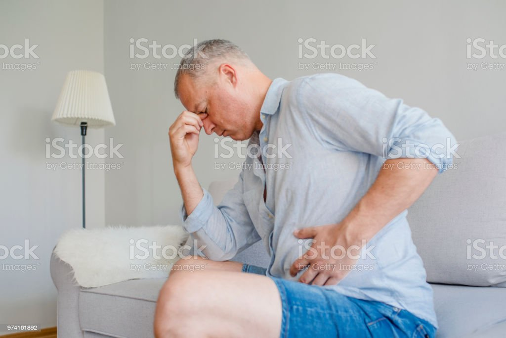 Disturbed male having pain in stomach stock photo