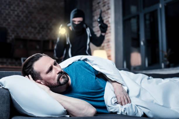 Homem perturbado, acordando e um ladrão que está por trás dele - foto de acervo