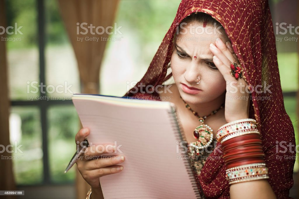 Disturbed newly married Indian, young woman reading on notepad. stock photo
