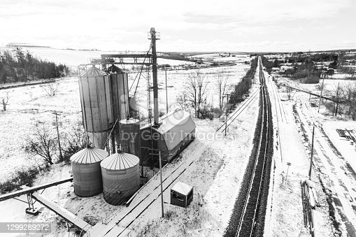 Aerial drone view of disused grain silos at the edge of a rail line.