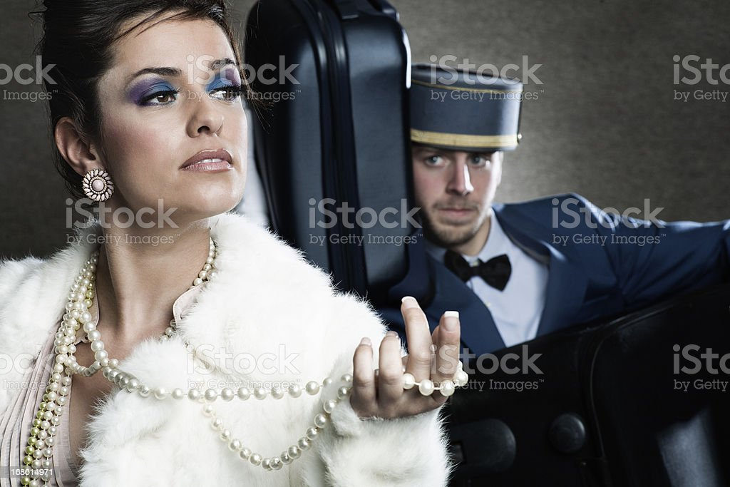 Diva in a hotel with bellboy carrying her luggage. stock photo