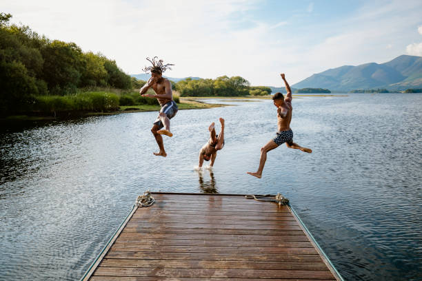 Dive Bomb Young multi ethnic guys jumping off a jetty into a lake in Derwent Water in Cumbria cumbria stock pictures, royalty-free photos & images