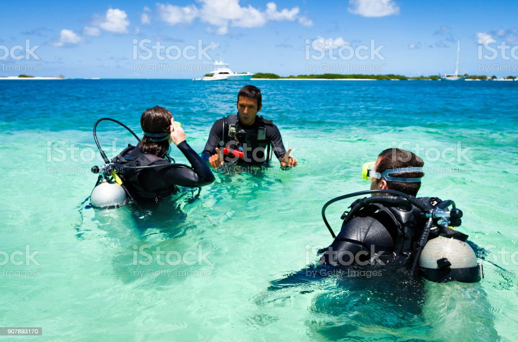 Dive master training a couple for first dive in a tropical turquoise island beach. stock photo