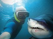 Underwater selfie with friend. Scuba diver and shark in deep sea.