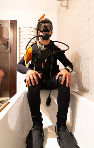 A diver dressed in scuba gear, in the bathtub. Home confinement stock photo