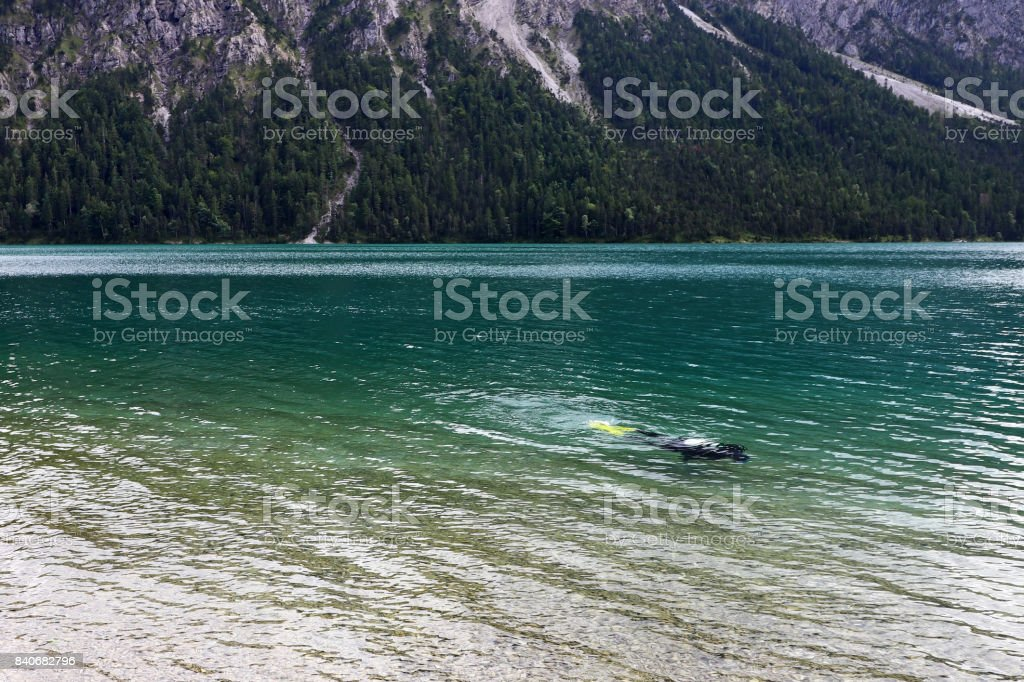 A diver in the turquoise blue water of the Plansee stock photo