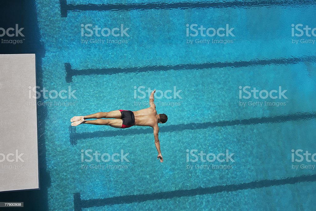 Diver midair going into pool stock photo